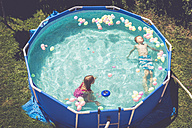 Boy and girl in swimming pool surrounded by balloons - SARF002067