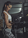 Portrait of a female athlete training with dumbbells in gym - MADF000485