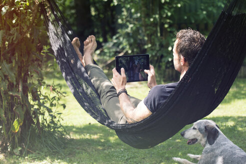 Relaxed man lying in hammock with digital tablet and dog beside him - ONF000833