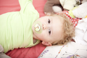 Portrait of little blond girl with pacifier lying on cot - MFRF000302