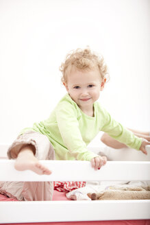 Portrait of little blond girl standing in cot - MFRF000304