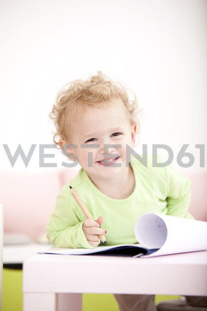Portrait of grinning little blond girl with coloured pencil - MFRF000305