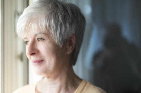 Portrait of smiling senior woman looking through window - FRF000293