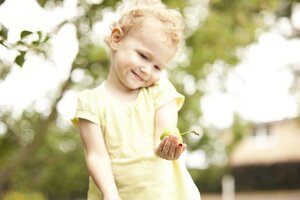 Little girl standing in the garden with apple in her hand - MFRF000319