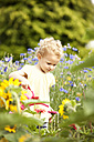 Little girl standing in the garden watering flowers - MFRF000324