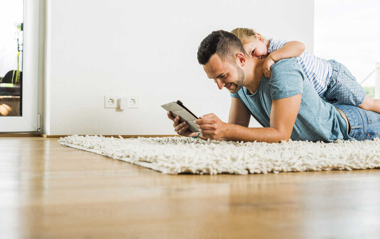 Happy father and daughter lying on rug using digital tablet - UUF005161 - Uwe Umstätter/Westend61