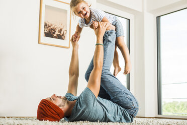 Father lying in rug lifting up happy daughter - UUF005209