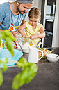 Father and daughter baking in kitchen - UUF005166