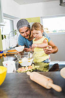 Father and daughter baking in kitchen - UUF005168