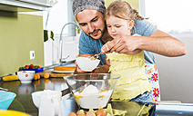 Father and daughter baking in kitchen - UUF005170