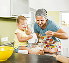 Father and daughter baking in kitchen - UUF005173