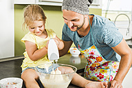 Father and daughter baking in kitchen - UUF005174