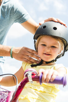 Father checking daughter's helmet on bike - UUF005187