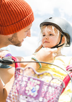 Father closing daughter's helmet on bike - UUF005188