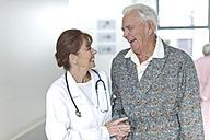 Doctor with happy elderly patient on hospital floor - ZEF007235
