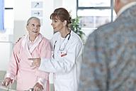 Doctor leading elderly patient on hospital floor - ZEF007236