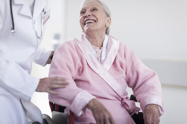 Doctor and smiling elderly patient in wheelchair - ZEF007245
