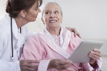 Doctor and smiling elderly patient in wheelchair with digital tablet - ZEF007246