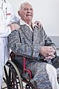 Doctor and smiling elderly patient in wheelchair - ZEF007251