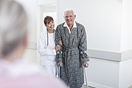 Doctor leading elderly patient with crutches on hospital floor - ZEF007253