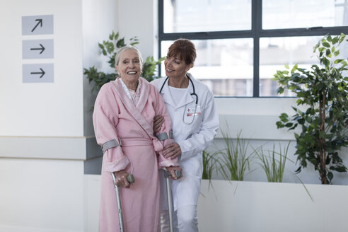 Doctor leading elderly patient with crutches on hospital floor - ZEF007262