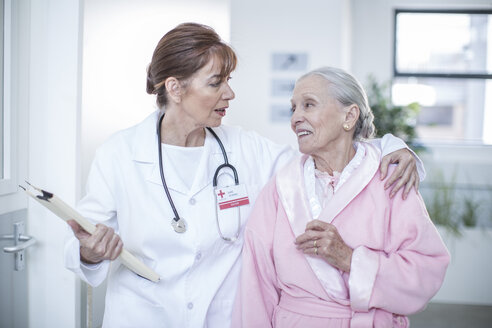 Doctor and smiling elderly patient on hospital floor - ZEF007255
