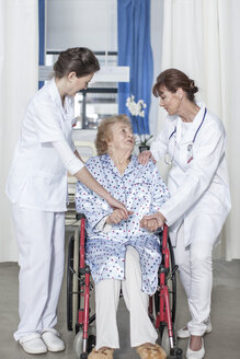 Doctor and nurse caring for elderly patient in wheelchair - ZEF007275