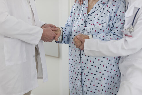 Two doctors holding hands of elderly patient - ZEF007282