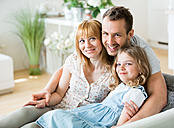 Happy family sitting on couch - WESTF021495