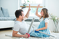 Father and daughter playing with toy swords, giving high five - WESTF021552