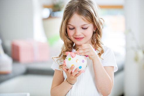 Girl throwing coin into piggy bank - WESTF021564