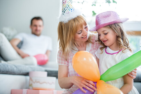 Family celebrating with balloons and party hats - WESTF021576