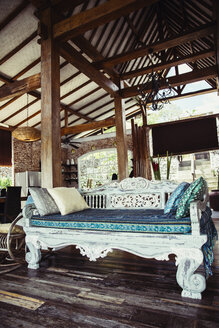 Indonesia, Bali, wooden classic Indonesian daybed in a holiday villa - MBEF001400