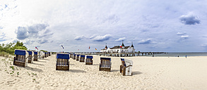 Germany, Ahlbeck, view to sea bridge with hooded beach chairs on the beach in the foreground - PUF000393