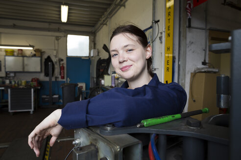 Young woman working in repair garage, looking at camera - SGF001802