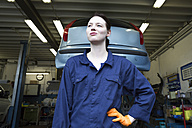 Young woman working in repair garage, standing in front of hoist - SGF001810