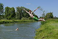 Germany, Bavaria, teenage boy jumping into River Loisach - LBF001160
