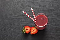 Glass of strawberry smoothie and sliced strawberry - CSF025974