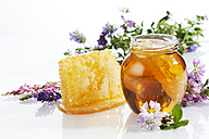 Glass of blossom honey with honeycomb and blossoms on white ground - CSF025979