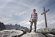 Germany, Bavaria, Osterfelderkopf, man standing at summit cross - RBF003013