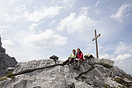 Germany, Bavaria, Osterfelderkopf, couple resting at summit cross - RBF003016