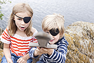 Boy and girl dressed up as pirates at a rock - MFRF000285