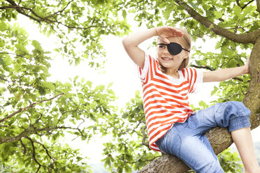 Girl dressed up as pirate sitting on a tree looking out - MFRF000283