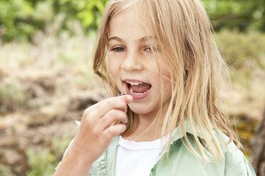 Blond girl eating a blueberry - MFRF000280