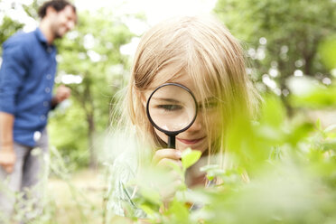 Girl in the nature looking through magnifying glass - MFRF000277