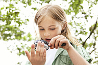 Girl looking through magnifying glass - MFRF000274