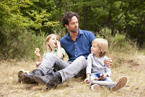Father with two children having a picnic at forest edge - MFRF000271