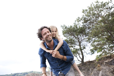 Father carrying happy daughter piggyback - MFRF000267