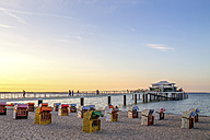 Germany, Niendorf, view to Timmendorfer Strand with hooded beach chairs and sea bridge - PUF000405