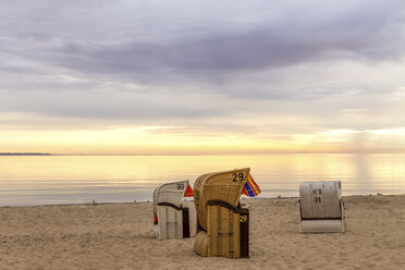 Germany, Niendorf, three hooded beach chairs on Timmendorfer Strand at sunrise - PUF000402